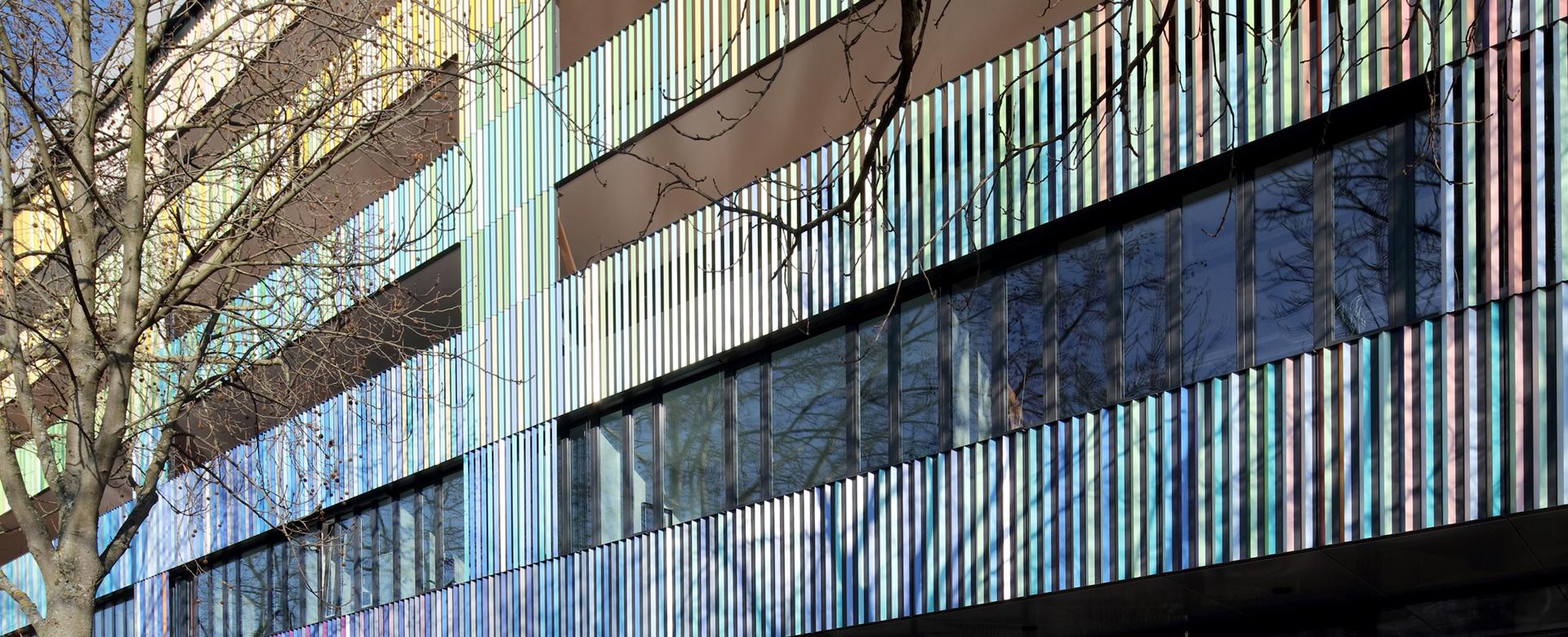 Fassadenlamellen des Marrahauses in Blau-, Grün- und Gelbtönen