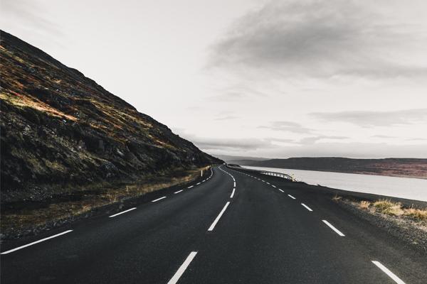 Menschenleere Landschaft, in der ene Straße Richtung Horizont führt.