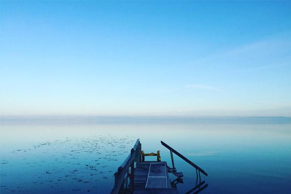 Steg, der aufs offene Meer führt und den Blick auf einen weiten Horizont freigibt