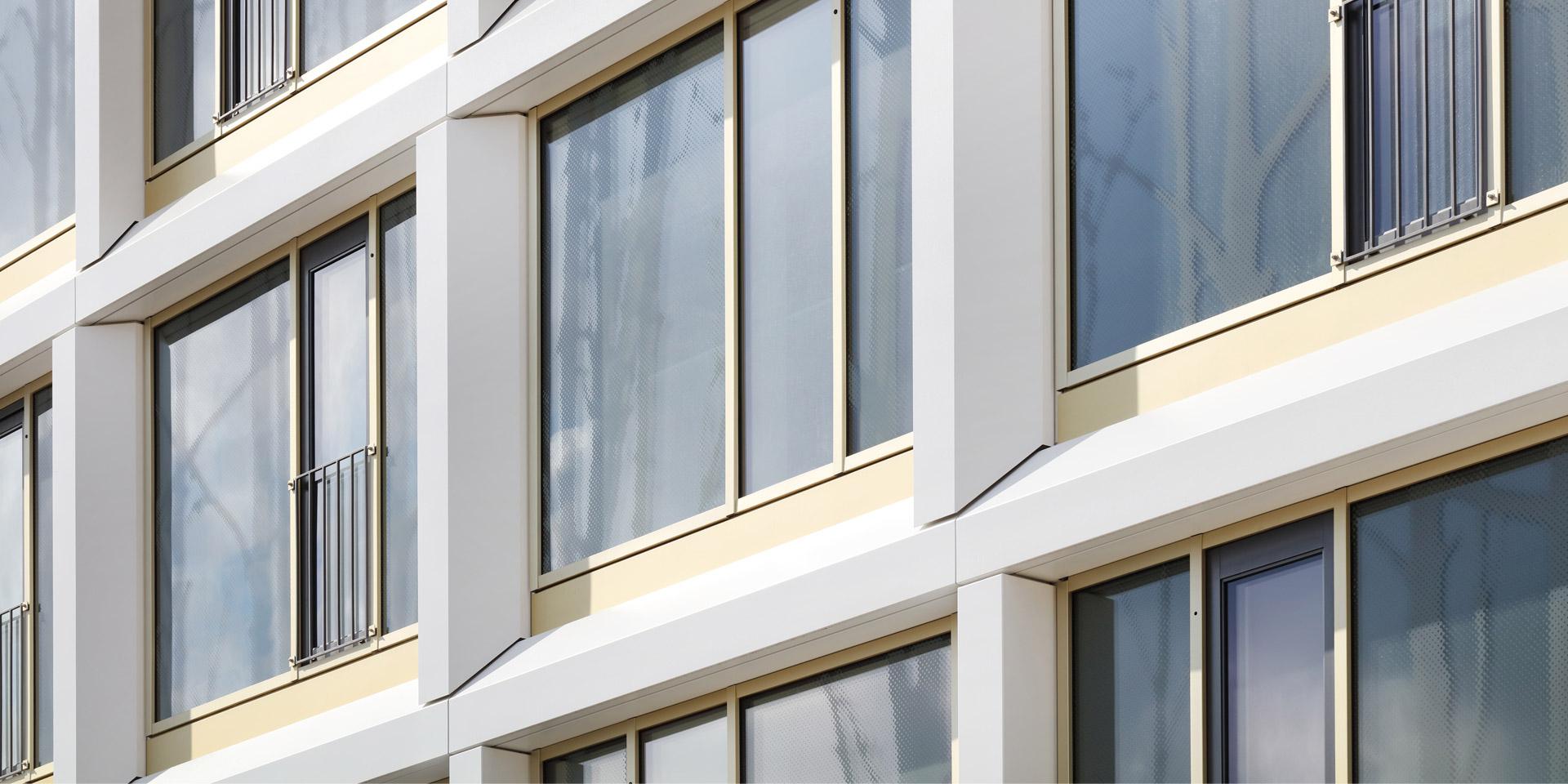 Fassadendetail des Wohnquartiers am Lettenwald in Ulm mit fein strukturierten Profilen und Blechen in Duraflon RAL 9016 Struktur.