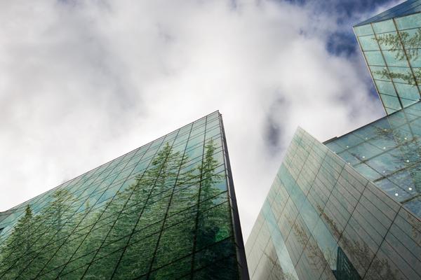 Gebäude mit Spiegelung von Bäumen auf der Fassade