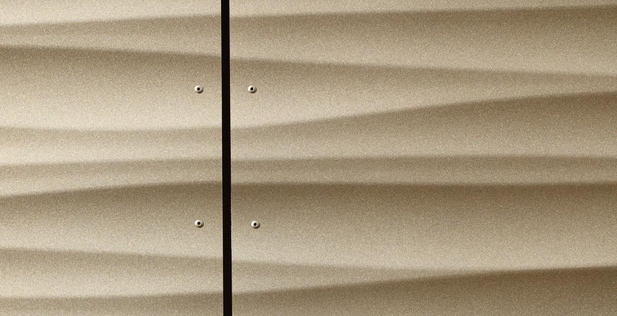 Fassadenblech mit 3D-Effekt in Duraflon Metallisé Glimmer sandgold matt, verbaut am Rupert-Ness Schulzentrum in Ottobeuren.