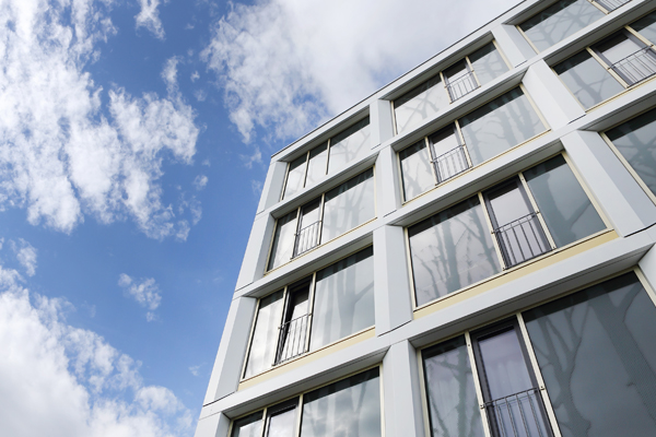 Fassadenansicht Referenz Wohnquartier am Lettenwald in Ulm mit strahlend weißer Fassade in Duraflon Feinstruktur