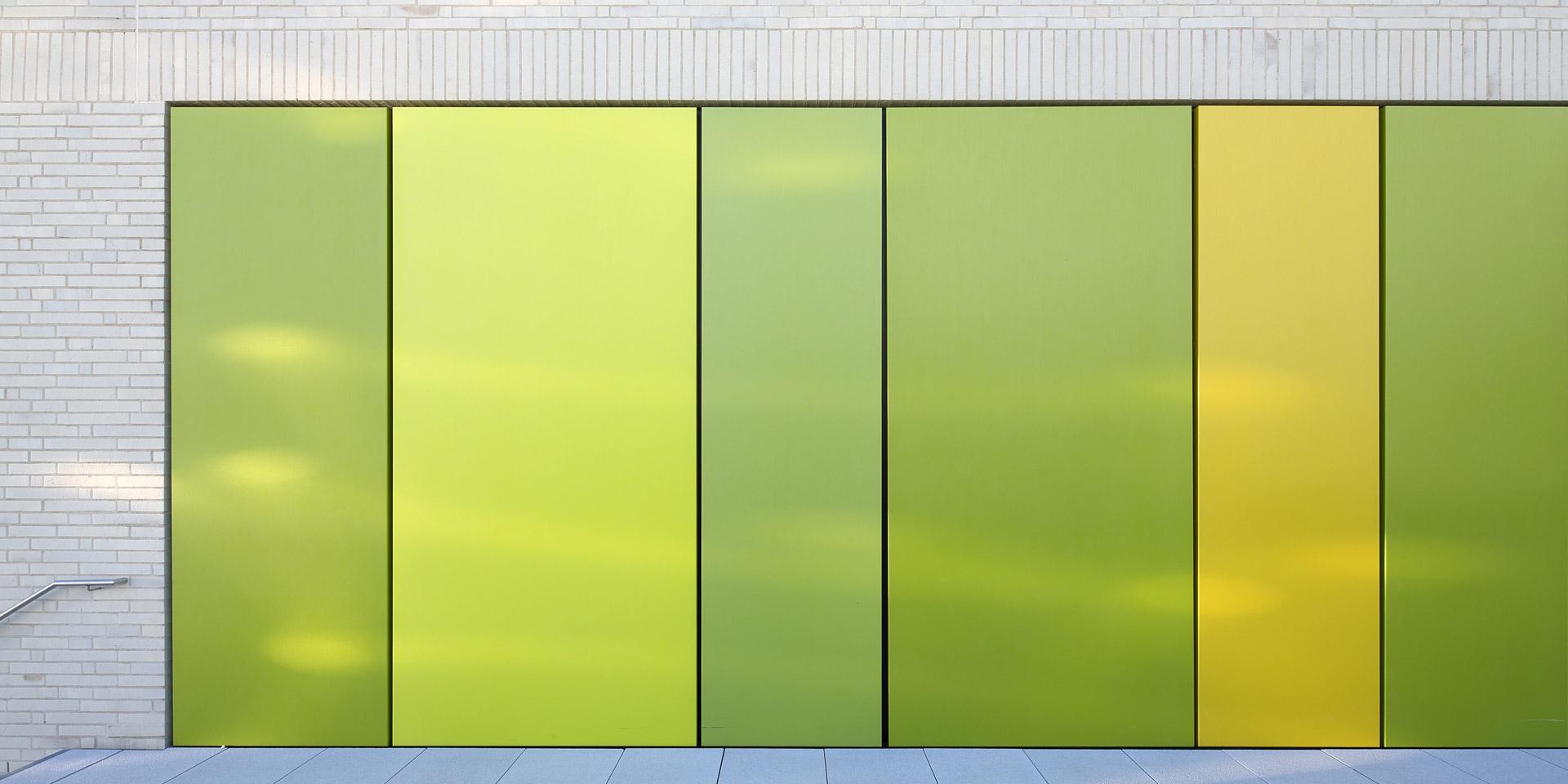 Detail des Gymnasiums in Trudering von felix schürmann ellen dettinger architekten mit farbintensiven grünen und gelben Fassadenblechen.