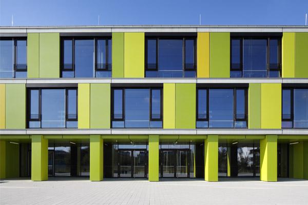 Gymnasium in Trudering mit grün-gelben Fassadenflächen in Duraflon