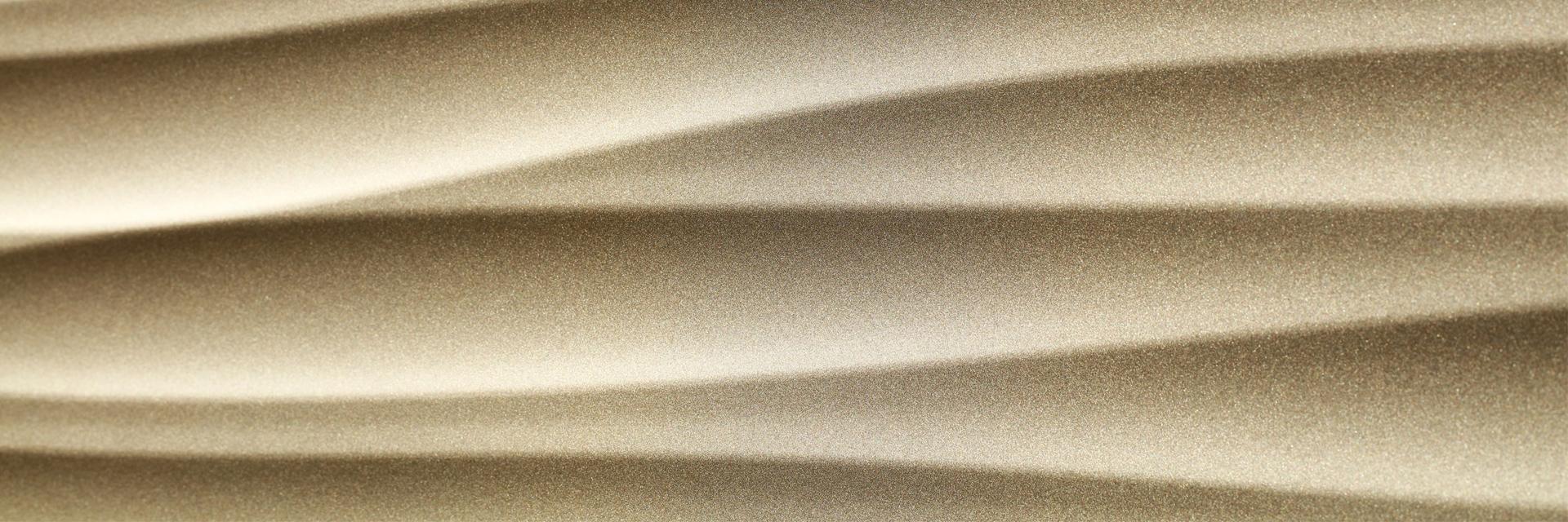 Dreidimensional geformtes Fassadenblech, beschichtet mit Duraflon Metallisé Glimmer sandgold matt